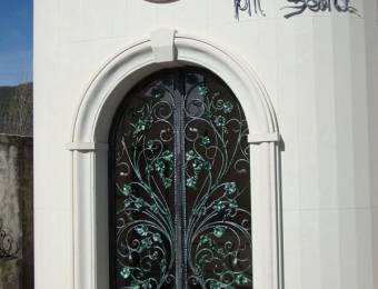 Wrought iron door with green decorations