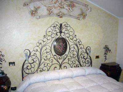 Wrought iron bed with decorated headboard and centre medallion